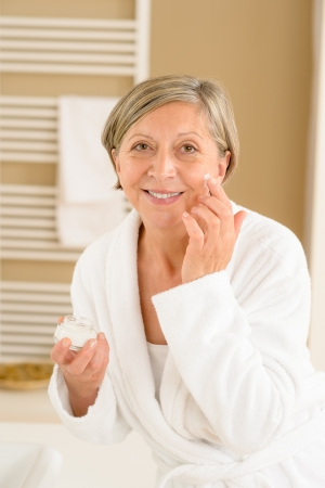 Senior woman hold anti-wrinkles cream in bathroom looking at camera photo