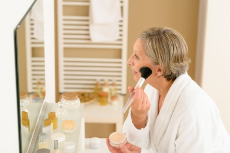 Senior woman apply make-up powder in front of bathroom mirror Stock Photo - 14900053