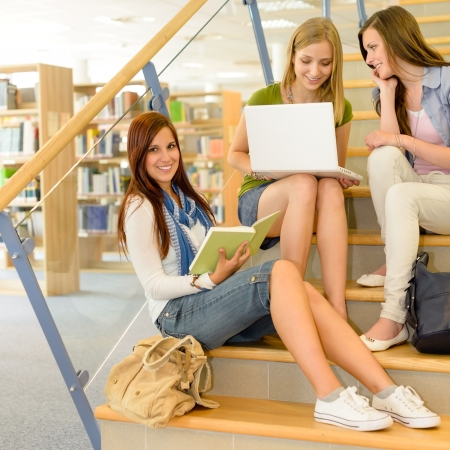 three shelves: Three teenage female studying together on high school library stairs