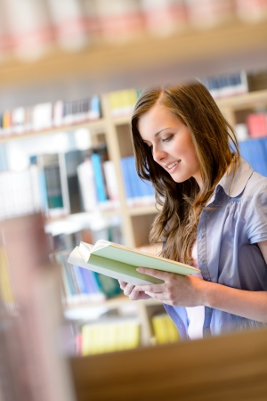 Young student woman reading book among library shelves photo