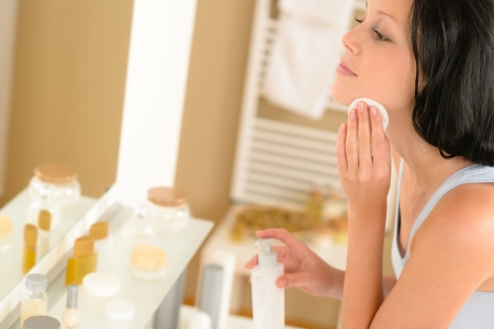 Young woman in bathroom clean face make-up removal looking mirror Stock Photo - 14961857