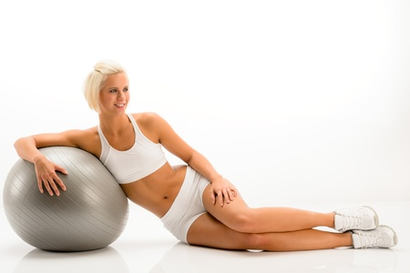 Sportive woman leaning on gym ball on white background photo