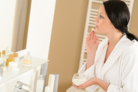 woman face cream: Woman looking in bathroom mirror and applying face moisturizer cream Stock Photo