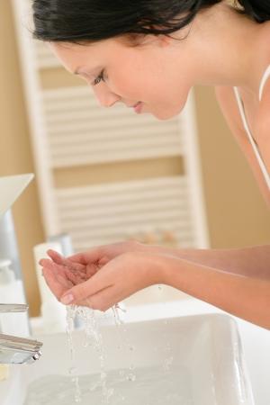 wash basin: Young woman in bathroom washing her face at wash basin Stock Photo