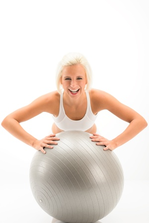 Smiling woman exercising on fitness ball on white background photo