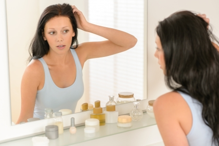 Young brunette woman in bathroom looking at herself in mirror Stock Photo - 14994835