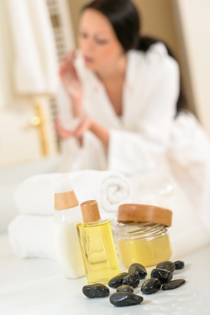 Close-up body care products in bathroom with woman in background photo