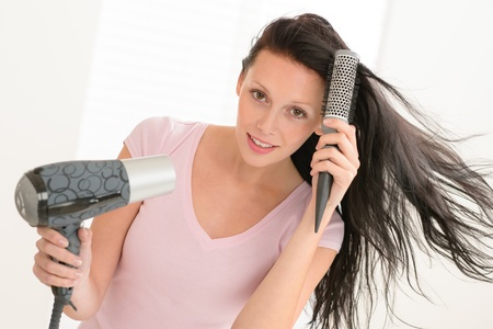 Brunette woman blow-drying long hair using round hairbrush photo