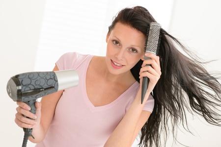 Brunette woman blow-drying long hair using round hairbrush photo