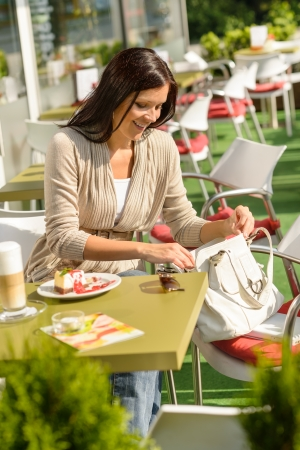 Woman about to pay looking purse at cafe bar smiling Stock Photo - 15035977