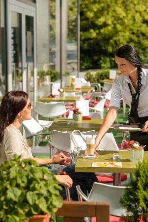 cafe bar: Serveerster serveren vrouw latte in cafe bar terras zonnige dag
