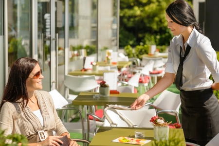 pay desk: Waitress giving back to woman change money bill restaurant terrace Stock Photo