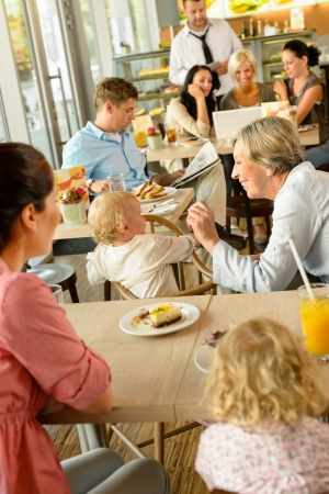 Mother and grandmother with children at cafe eating cake women photo