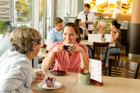 Senior woman with her daughter at cafe drinking eating happy Stock Photo - 15035962