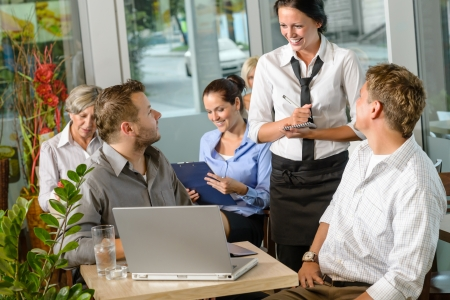Waitress taking order from businessmen in cafe smiling laptop work photo