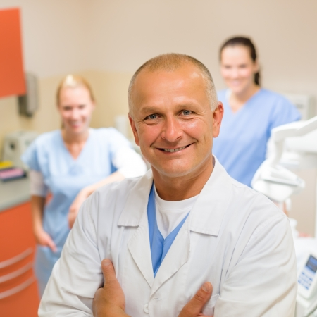 Smiling male dentist posing with female assistants at office photo