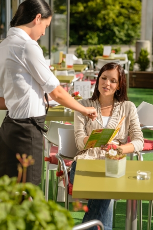 taking a break: Waitress point menu woman in cafe bar terrace order food Stock Photo