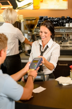 Man paying bill at cafe using card bill happy waitress photo