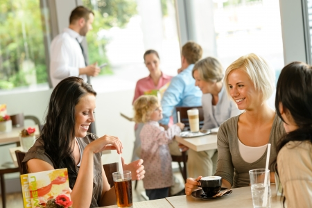 social gathering: Women friends enjoying a drink at cafe talking happy relaxing