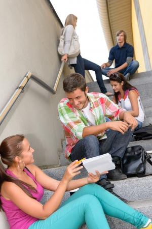 Students talking relaxing on school steps teens break smiling campus photo