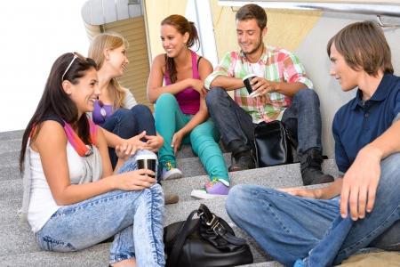 adolescentes riendo: Los estudiantes re�an en las escaleras de la escuela en la universidad adolescentes descanso relajante