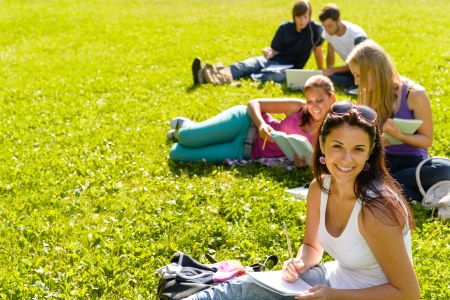 studious: Students studying sitting on grass in park happy teens campus Stock Photo