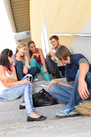 teenagers laughing: Students laughing on school stairs in break teens college relaxing