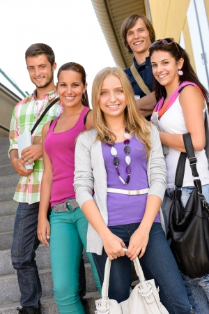 Students back to school on college stairs teens standing smiling photo