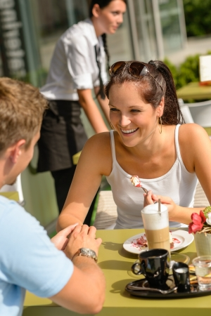Couple enjoy coffee dessert restaurant sunny terrace eat cheesecake photo