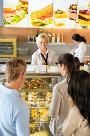 customers: Customers waiting in line to buy dessert woman man cafe Stock Photo