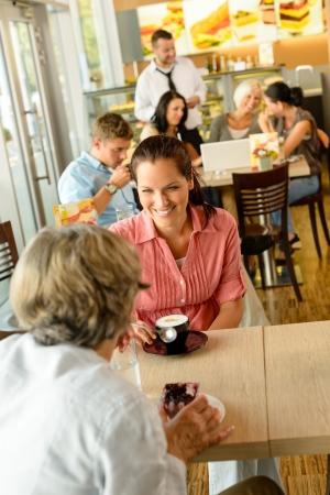 tomando café: Superior de la mujer con su hija en beber café comiendo feliz