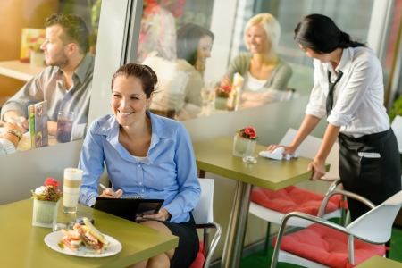 diners: Businesswoman working in lunch break in cafe writing happy inspiration