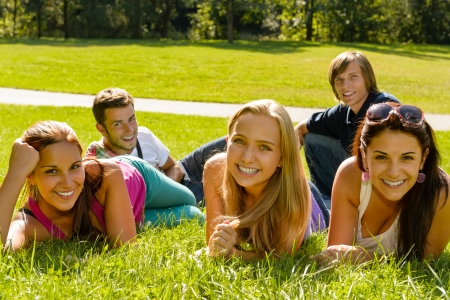 group of teens: Students laying on grass in park campus smiling relaxing happy