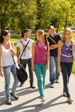school teens: Los estudiantes que caminan a la escuela amigos adolescentes felices campus de grupos juveniles Foto de archivo