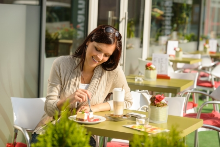 Woman at cafe terrace eating cheesecake dessert  smiling sunny day photo