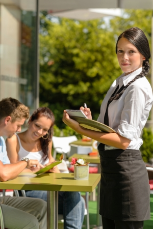 vertical bar: Waitress waiting for clients to decide cafe order restaurant terrace