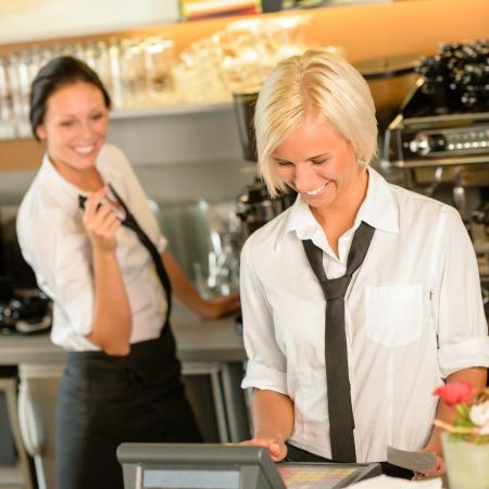 카페 웨이트리스가 주문 법안 레지스터 여성이 행복한 작업에 현금화 하시니까 스톡 콘텐츠