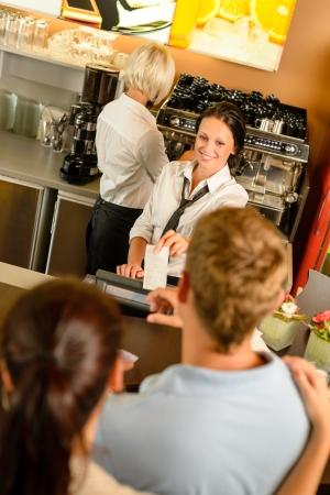 cash register: Cafe employee woman giving man bill receipt woman customer bar Stock Photo