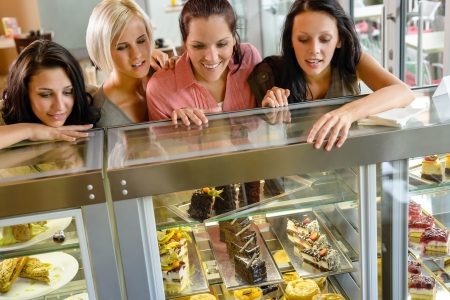 Women friends looking at cakes in cafe craving window display Stock Photo - 15099353