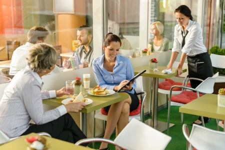 cafeteria: Businesswomen talking business in lunch break cafe happy working showing