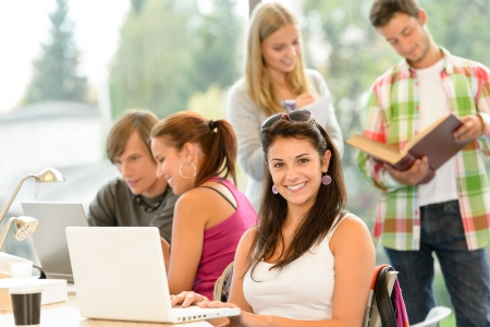 Teens studying in high-school library young pupils smiling laptop book photo
