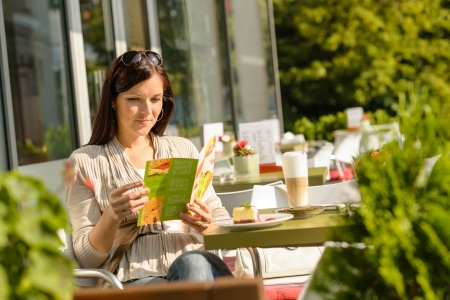 Woman looking at menu sitting cafe bar terrace choice dessert photo