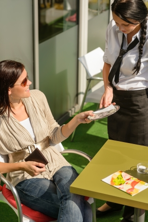 Woman paying bill to waitress cafe restaurant give tip happy Stock Photo