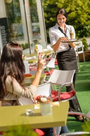 bringing: Waitress bringing woman her order coffee cafe restaurant terrace
