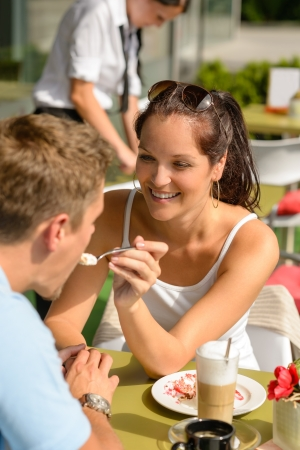 Woman feeding man cheesecake at cafe couple flirting romantic happy photo