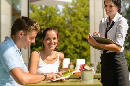 Couple at cafe ordering from menu waitress man point menu photo