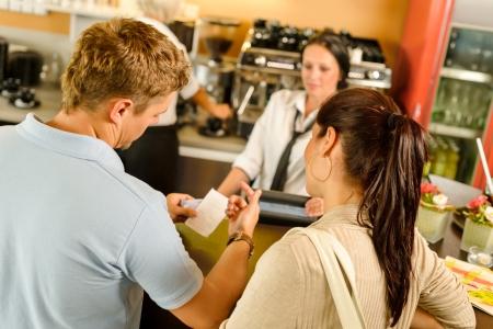 Hombre de cheques recepción en el restaurante bar café pareja pago camarera