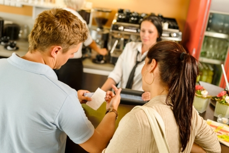 Man checking receipt at cafe restaurant payment waitress couple bar photo