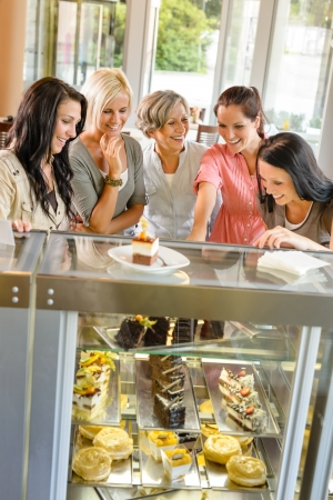Group of friends looking at cakes cafe women happy choosing