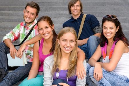 high school students: Los estudiantes que se sientan en las escaleras de la escuela sonriendo adolescentes amigos de la universidad del campus